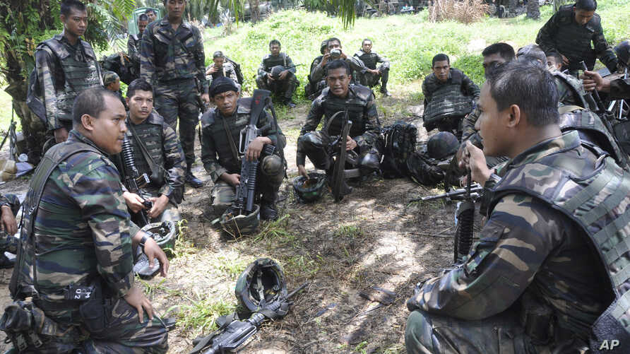 Malaysian soldiers confer during an operation in Sungai Nyamuk, a village adjacent to Kampung Tanduo, Malaysia, March 14, 2013. A contingent of Malasian troops is now heading ro Somalia.