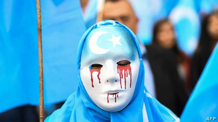 A person wearing a white mask with tears of blood takes part in a protest march of ethnic Uighurs during a demonstration around the EU institutions in Brussels.