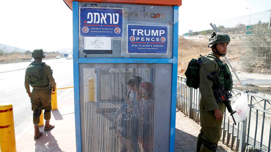Israeli soldiers stand near a bus stop covered with posters from the Israeli branch of the U.S. Republican party campaign in support of Donald Trump on October 6, 2016.