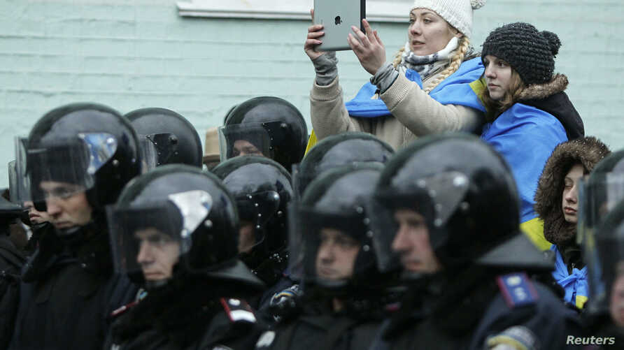 A supporter of the pro-presidential Party of the Regions takes pictures of a rally to support EU integration, with riot police and Interior Ministry personnel blocking a street in the foreground, in central Kiev, December 8, 2013. Ukraine's oppositio