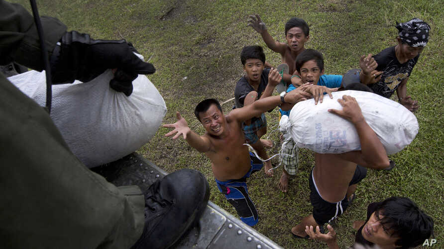 Villagers affected by last week's Typhoon Haiyan scramble for aid from a U.S. Navy Sea Hawk helicopter from the U.S. aircraft carrier USS George Washington in the coastal town of Tanawan, central Philippines. Nov. 17,  2013.