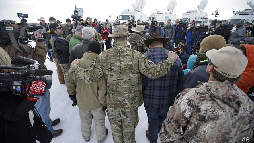 Members of the group occupying the Malheur National Wildlife Refuge headquarters hug after Ammon Bundy, center, left, one of the sons of Nevada rancher Cliven Bundy, spoke with reporters during a news conference Monday, Jan. 4, 2016, near Burns, Oreg