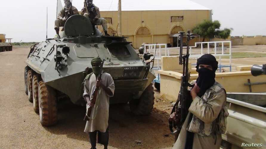 Fighters from the Al Qaeda-linked Islamist group MUJWA stand guard in Gao, northern Mali, August 7, 2012.