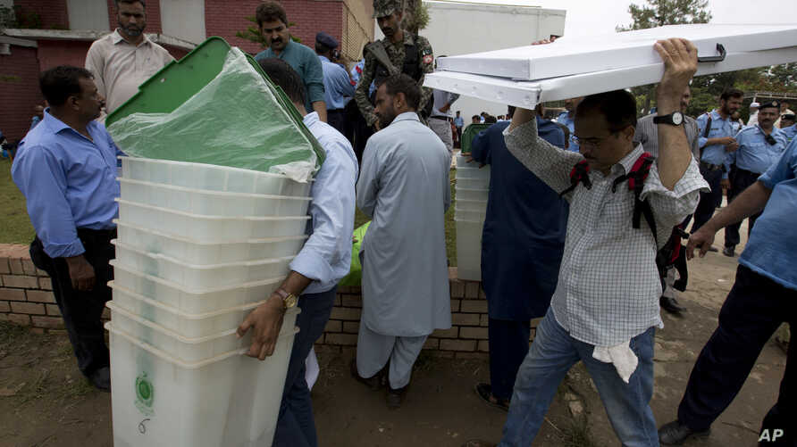 Pakistani election staff carry polling material to stations at a distribution center in Islamabad, Pakistan, July 24, 2018.