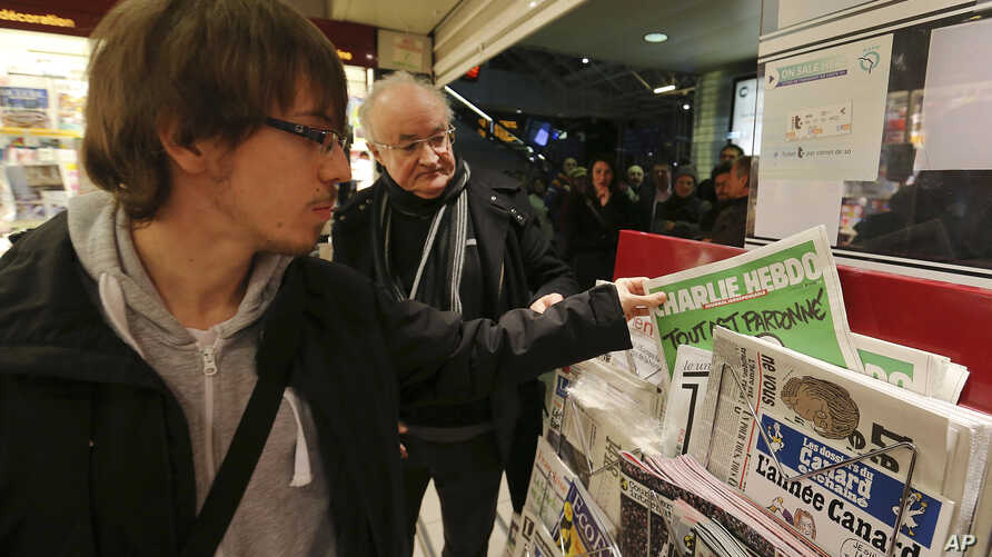 A man picks up a copy of Charlie Hebdo newspaper at a newsstand in Rennes, western France, Jan. 14, 2015.