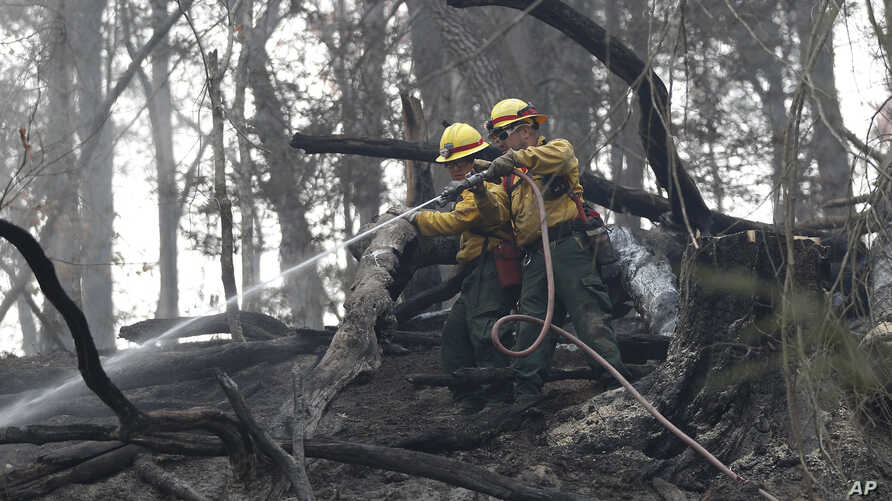 Firefighters Valarie Lopez, left, and Mark Tabaez work to cool hot spots after a wildfire burned a hillside in Clayton, Georgia. The fire zone has spread from northern Georgia and eastern Tennessee into eastern Kentucky and the western Carolinas.