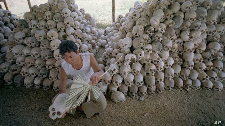 FILE - A man cleans a skull near a mass grave at the Chaung Ek torture camp run by the Khmer Rouge in this undated photo. The last surviving leaders of the communist Khmer Rouge regime were convicted of genocide, crimes against humanity and war crime