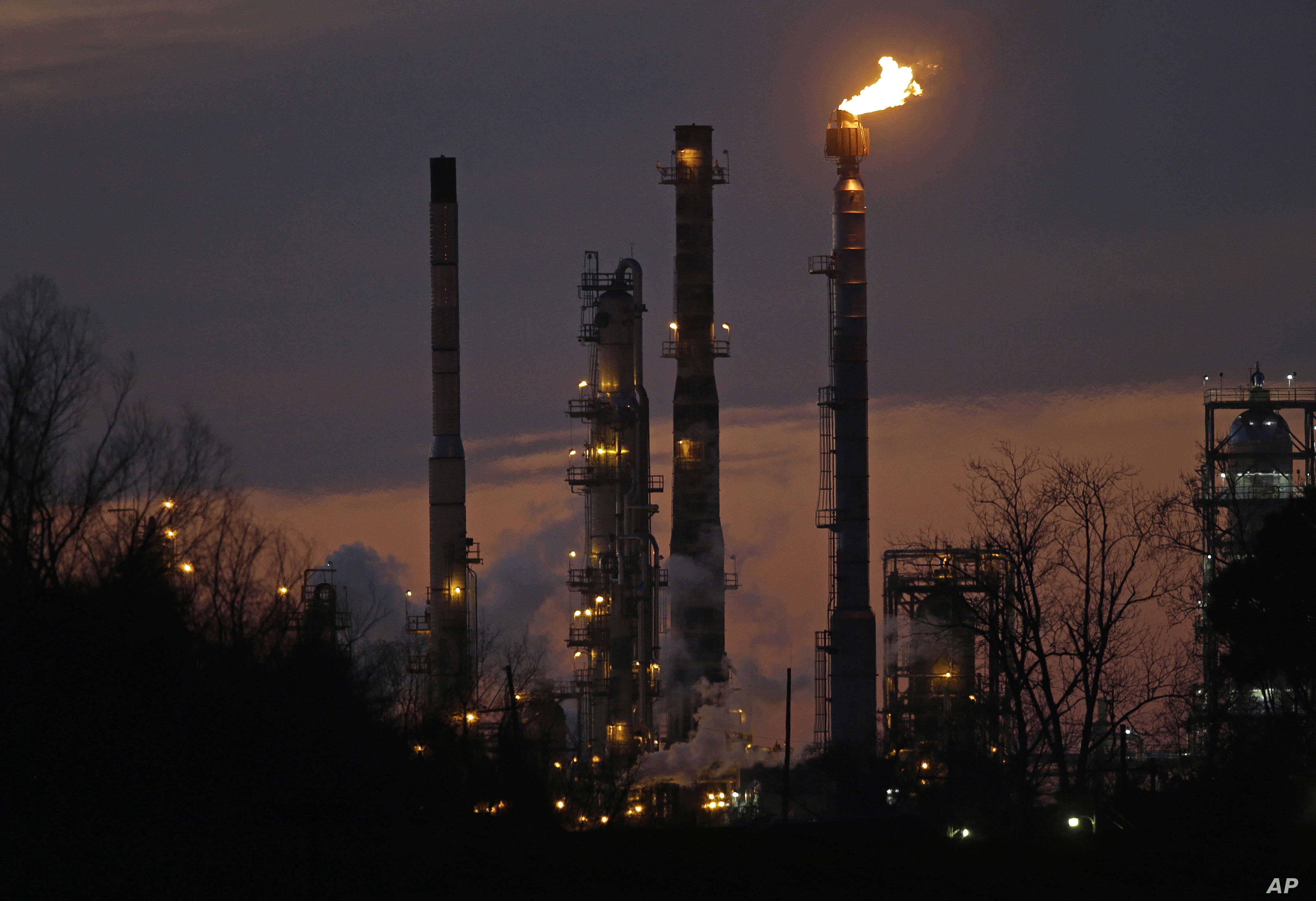 FILE - Stacks and burn-off from the ExxonMobil refinery are seen at dusk in St. Bernard Parish, Louisiana, Feb. 13, 2015.