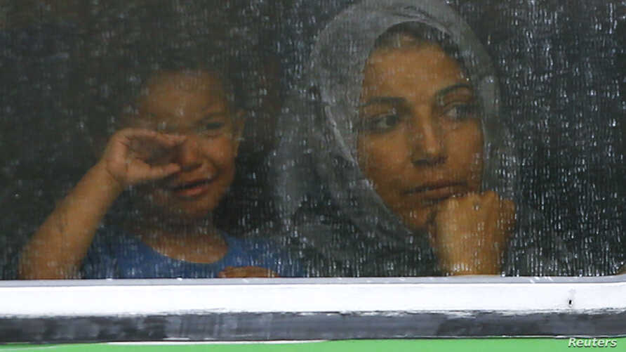 Migrants look out through the window of a train at the railway station in Bicske, Hungary, Sept. 4, 2015.
