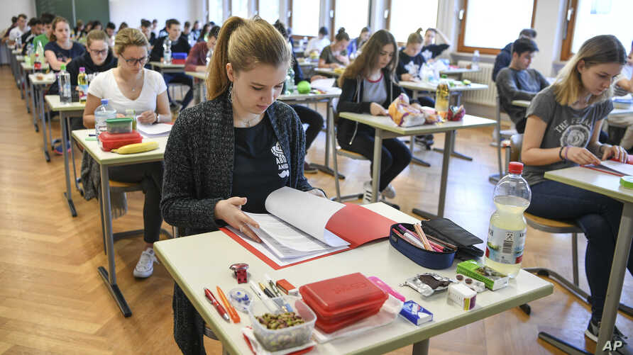 FILE - In this April 18, 2018 file photo students take a look at an exam test at the Graf-Zeppelin-Gymnasium in Friedrichshafen, Germany.