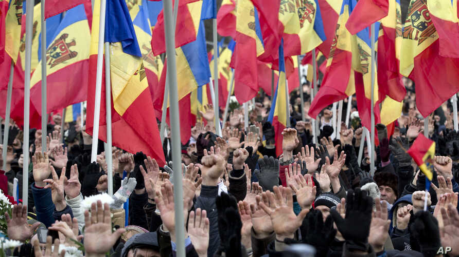 People raise their hands during a large protest in Chisinau, Moldova, Jan. 24, 2016.
