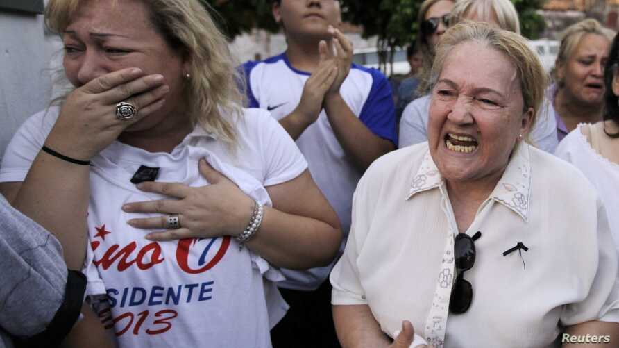 Supporters of the late Paraguayan presidential candidate Lino Cesar Oviedo react outside the morgue where his remains were taken after he died in a helicopter crash in Asuncion, Paraguay, Sunday, Feb. 3, 2013.