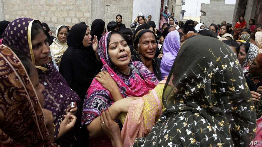Pakistani women mourn the death of a relatives killed from a fire in a factory in Karachi, Pakistan, Sept. 13, 2012.