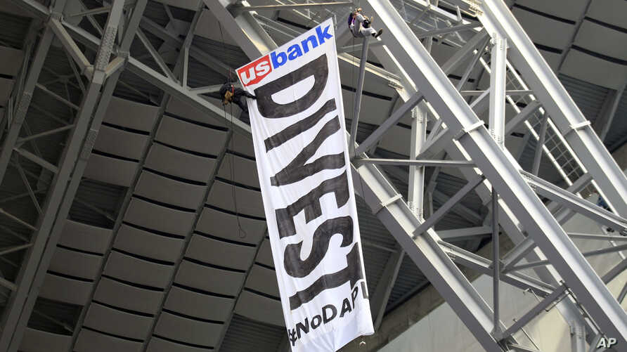 Protesters against the Dakota Access Pipeline rappel from the catwalk in U.S. Bank Stadium during the first half of an NFL football game between the Minnesota Vikings and the Chicago Bears, Jan. 1, 2017, in Minneapolis.