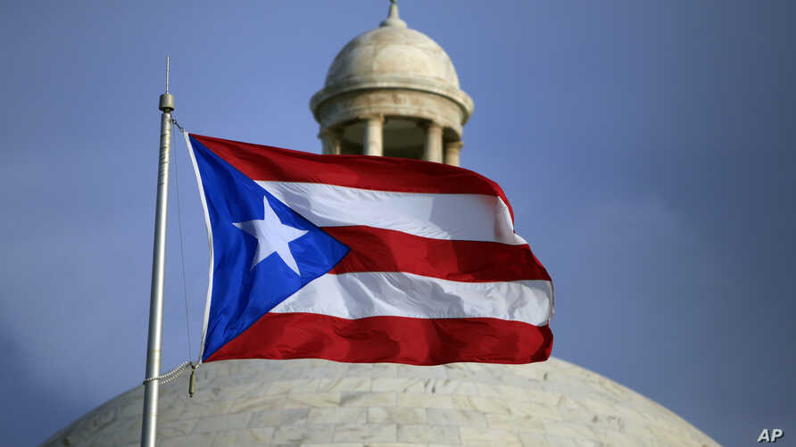 FILE - The Puerto Rican flag flies in front of Puerto Rico's Capitol as in San Juan, Puerto Rico, July 29, 2015.