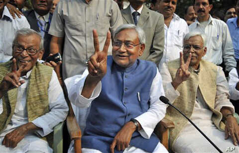 Bihar state Chief Minister Nitish Kumar, center, displays the victory sign during a press conference after his National Democratic Alliance won the state elections, in Patna, India, Nov. 24, 2010. Kumar, the top elected official of one of India's poo