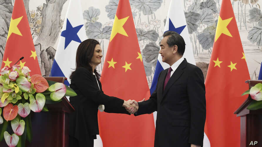 Panama's Foreign Minister Isabel de Saint Malo, left, shakes hands with her Chinese counterpart Wang Yi during a joint press briefing after signing a joint communique on establishing diplomatic relations, in Beijing, June 13, 2017.