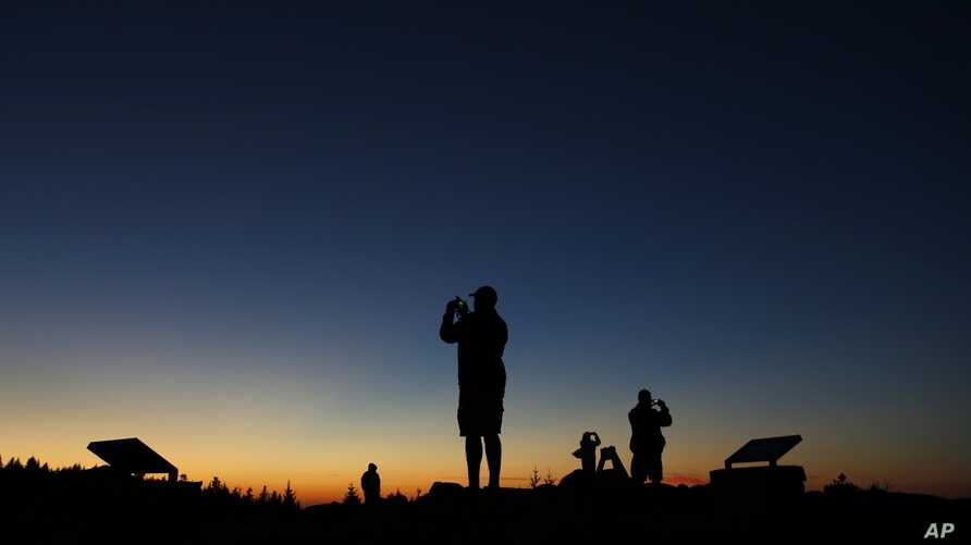 FILE - Tourists photograph the sunset at the summit of Cadillac Mountain in Acadia National Park near Bar Harbor, Maine, Oct. 2, 2014.