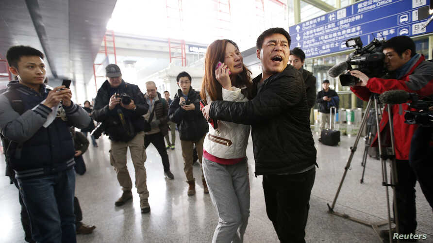 A relative of a passenger onboard Malaysia Airlines flight MH370 cries as she talks on her mobile phone at the Beijing Capital International Airport in Beijing, China, March 8, 2014.