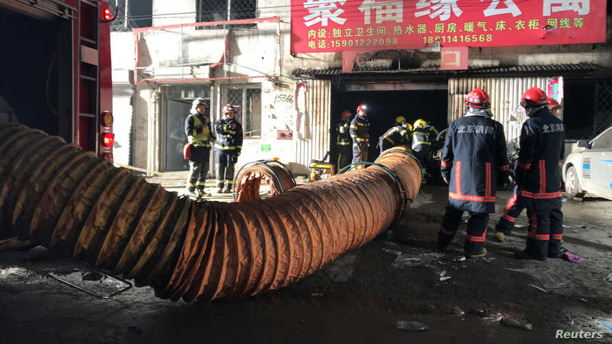 Firefighters work at the site of a house fire, in Daxing district, Beijing, early Nov. 19, 2017.