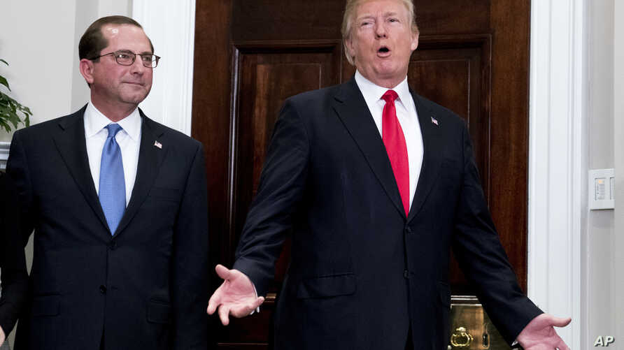 President Donald Trump, accompanied Health and Human Services Secretary Alex Azar (L), answers reporters' questions after participating in Azar's swearing in ceremony at the White House, Jan. 29, 2018.