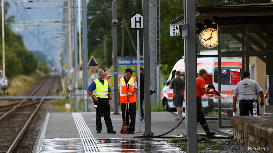 A Swiss police officer stands near workers cleaning a platform after a 27-year-old Swiss man's attack on a Swiss train at the railway station in the town of Salez, Switzerland, Aug. 13, 2016.