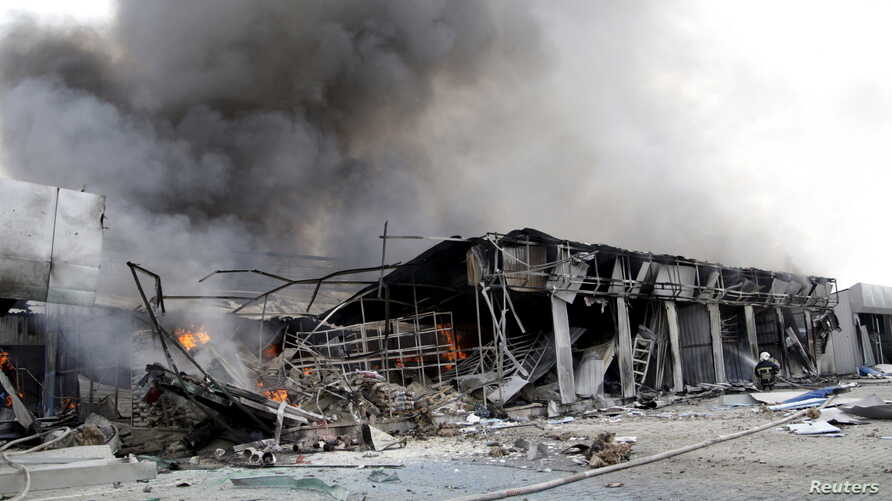 A firefighter works to extinguish a fire at a local market, which was recently damaged by shelling, Donetsk, Ukraine, June 3, 2015.