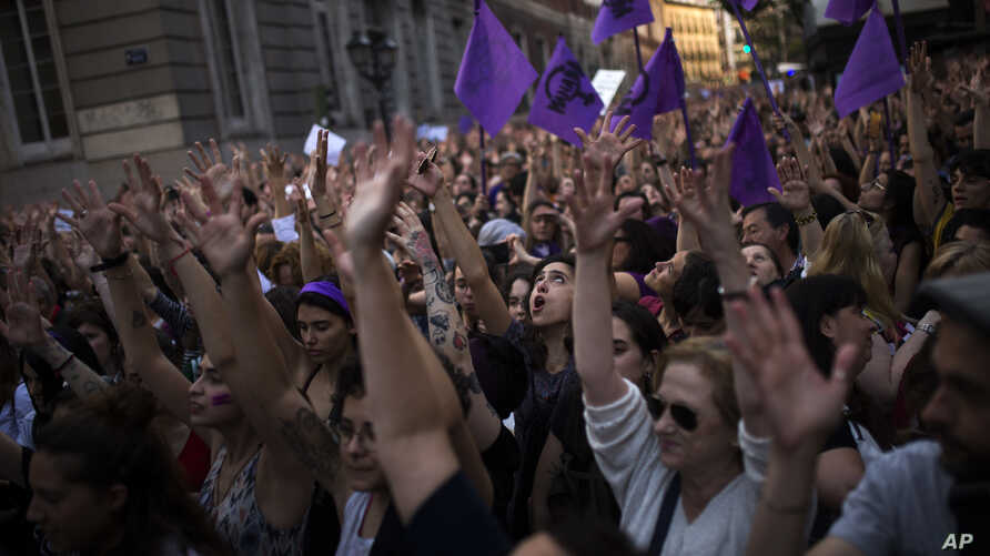 People lift up their arms as they shout slogans during a protest outside the Justice Ministry in Madrid, April 26, 2018.