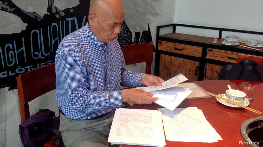 """FILE - Xu Xiaoshun, the father of activism blogger Wu Gan, who was detained in what is known as the """"709"""" crackdown, looks through documents about his son's case in a restaurant in Jiangsu Province, China, June 12, 2017."""