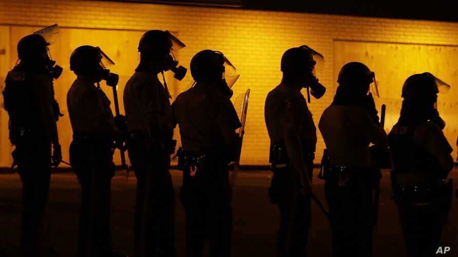 Police wait to advance after tear gas was used to disperse a crowd during a protest for Michael Brown in Ferguson, Mo., Sunday, Aug. 17, 2014.