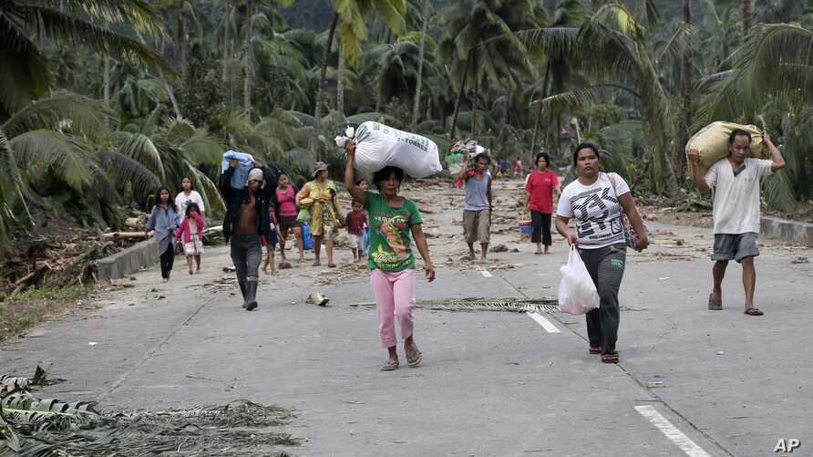 Residents evacuate to higher grounds at the flash flood-hit village of Andap, New Bataan township, Compostela Valley in southern Philippines Wednesday, Dec. 5, 2012.
