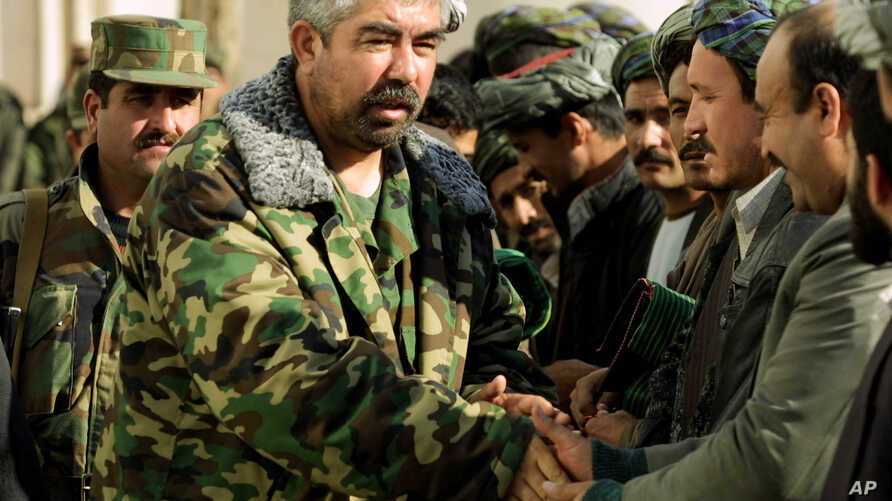 Afghan Deputy Defense Minister Rashid Dostum shakes hands with local residents in Shebergan, 125 km (78 miles) west of  Mazar-e-Sharif, northern Afghanistan, Thursday, Dec. 27 , 2001. Afghanistan's new interim leader, Prime Minister Hamid Karzai, app