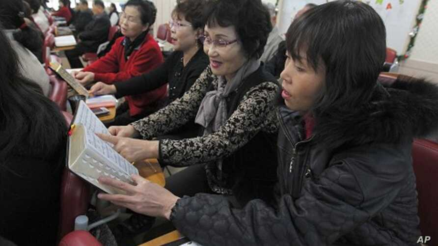 North Korean defectors sing hymns during a service at Saeteo Church in Seoul
