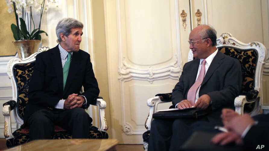 U.S. Secretary of State John Kerry, left, talks with Atomic Energy Agency (IAEA) Director General Yukiya Amano during a meeting at at hotel in Vienna, Austria, June 29, 2015.
