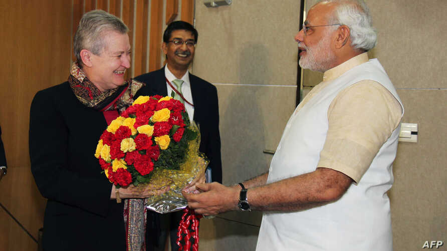 Chief Minister of the western Indian state of Gujarat and Bharatiya Janata Party (BJP) prime ministerial candidate Narendra Modi (R) presents a bouquet of flowers to US Ambassador to India Nancy Powell (L) as they meet in Gandhinagar in western Gujar