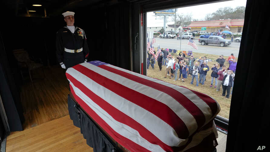 The flag-draped casket of former President George H.W. Bush passes through Magnolia, Texas, Dec. 6, 2018, along the route from Spring to College Station, Texas.