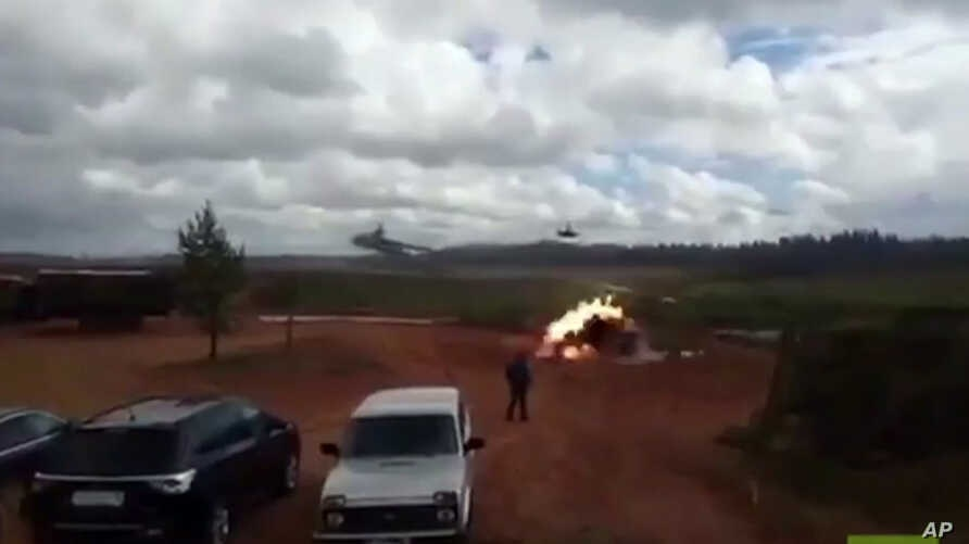 In this still made from an undated video provided by 66.ru, an explosion is seen after a helicopter fired a rocket in Luzhsky range, St. Petersburg region, Russia. A Russian military helicopter gunship accidentally fired on spectators during war game