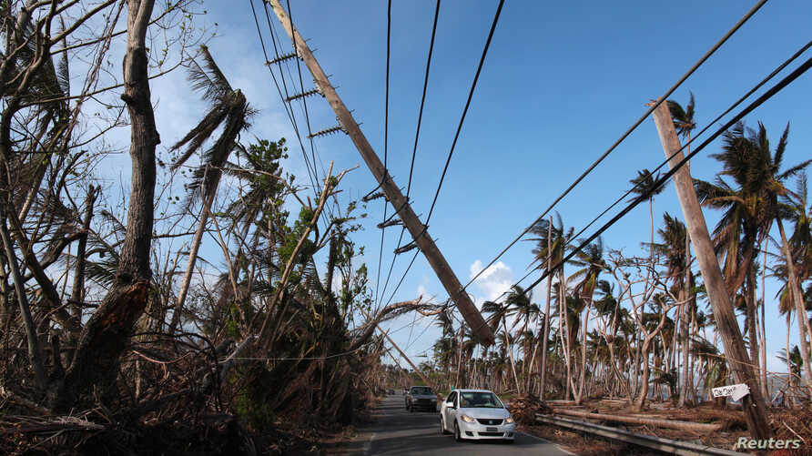 Cars drive under a partially collapsed utility pole, after the island was hit by Hurricane Maria in September, in Naguabo, Puerto Rico Oct. 20, 2017.