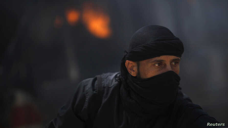 A fighter from the Islamist Syrian rebel group Jabhat al-Nusra is seen in front of a burning vehicle, caused by what activists said were missiles fired by a Syrian Air Force fighter jet from forces loyal to Syria's President Bashar al-Assad, at their