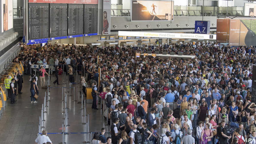 Passengers wait in a hall of Terminal 1 of the Frankfurt Airport, in Frankfurt Germany, Aug. 7, 2018 after parts of a terminal were evacuated over concerns that a security barrier was breached.