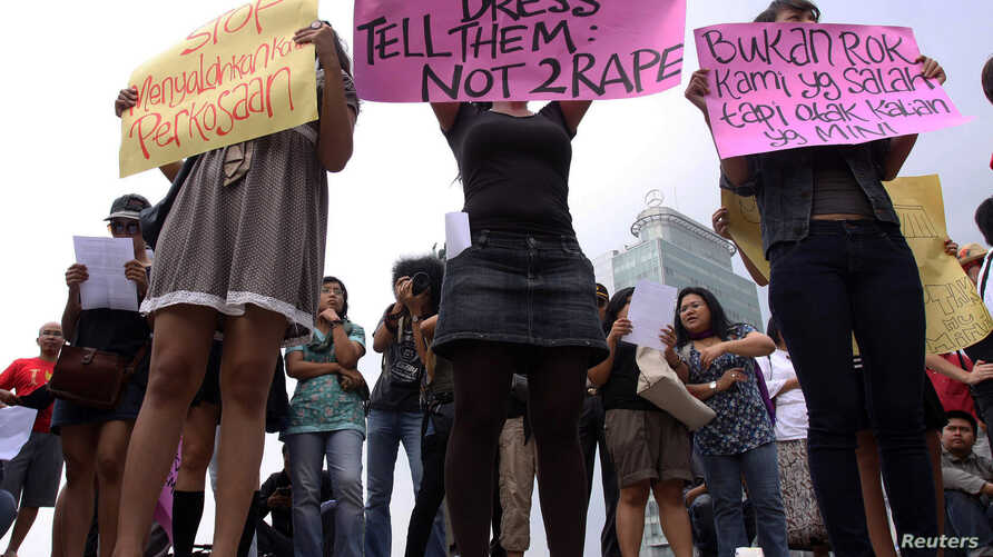 Women wearing miniskirts and tight leggings hold posters to protest against the idea that provocatively dressed women are to blame for sexual assaults, in Jakarta (September 2011 file photo)