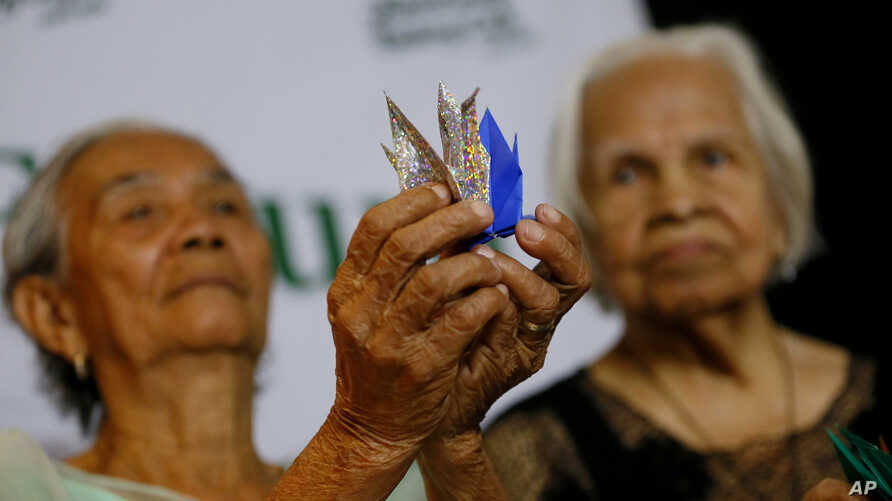 """Alleged Filipino """"comfort women"""" Narcisa Claveria, 85, left, and Hilaria Bustamante, 90, display Origami paper cranes to symbolize peace during a forum to demand justice, compensation and apology from the Japanese government for their alleged WWII or"""