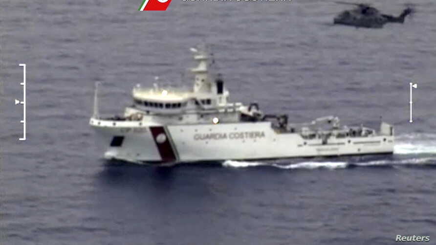 An Italian coast guard vessel is seen with an helicopter during the search and rescue operation underway after a boat carrying migrants capsized overnight, with up to 700 feared dead, in this still image taken from video, April 19, 2015.