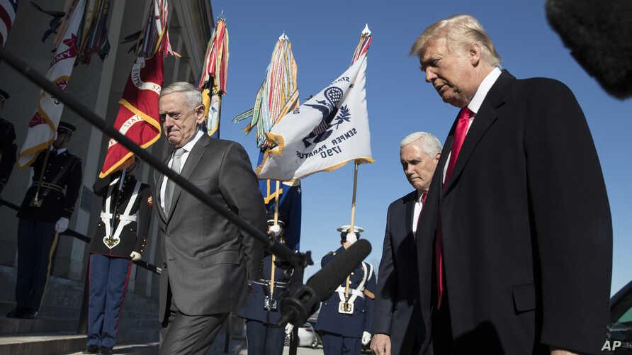President Donald Trump, joined by Defense Secretary Jim Mattis, left, and Vice President Mike Pence, walks into the Pentagon, Jan. 18, 2018, after speaking to the media.
