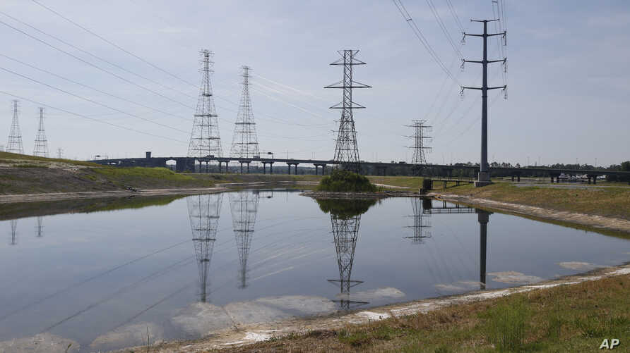 FILE - In this June 27, 2016, file photo, power lines tower over a coal ash pond from an abandoned coal fired power plant in Chesapeake, Virginia.