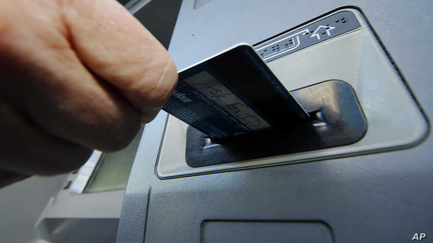 FILE - A person inserts a debit card into an ATM in Pittsburgh, PA.