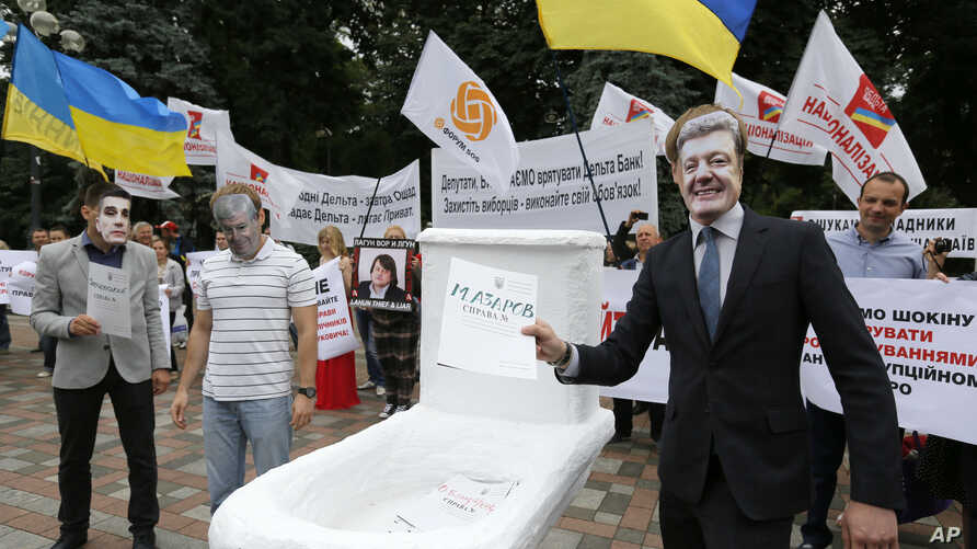 FILE - Anti-corruption activists hold a rally outside parliament in Kiev, Ukraine, on June 15, 2015. The rally organizers put a toilet seat on display as a symbol of what they feel is the effort by top officials to flush away politically inconvenient
