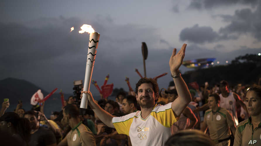 Leonardo Espindola carries the Olympic torch on its way to Rio de Janeiro for the opening ceremony of Rio's 2016 Summer Olympics, in Niteroi, Brazil on Aug. 2, 2016