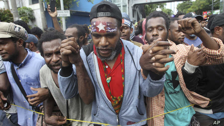 "A Papuan activist with his forehead painted with banned separatist flag the ""Morning Star"" marches with others during a rally commemorating the 57th anniversary of the failed efforts by Papuan tribal chiefs to declare independence from Dutch colonial"