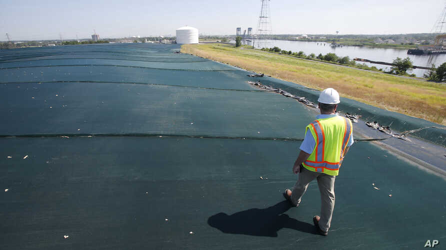 Project manager Jeff Richey, walks along the non-permeable cover of Coal Ash Basin B along the banks of the Elizabeth River in Chesapeake, Virginia, June 27, 2016.
